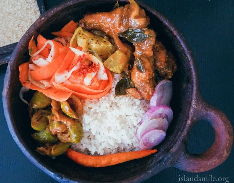A meal in a bowl, Rice, Yellow Cucumber cooked in coconut milk, Dry Thai egg-plant curry, a salad of carrot ribbons, chicken drumsticks baked and cooked in a gravy with Srilankan spices.
