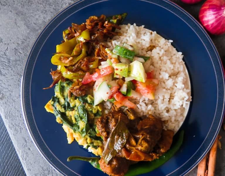 A srilankan meal with rice, dhal and spinach, chicken cooked in a mix of spice and yoghurt, a cucumber salad and a dry curry of capsicum, onion and dried shrimp.