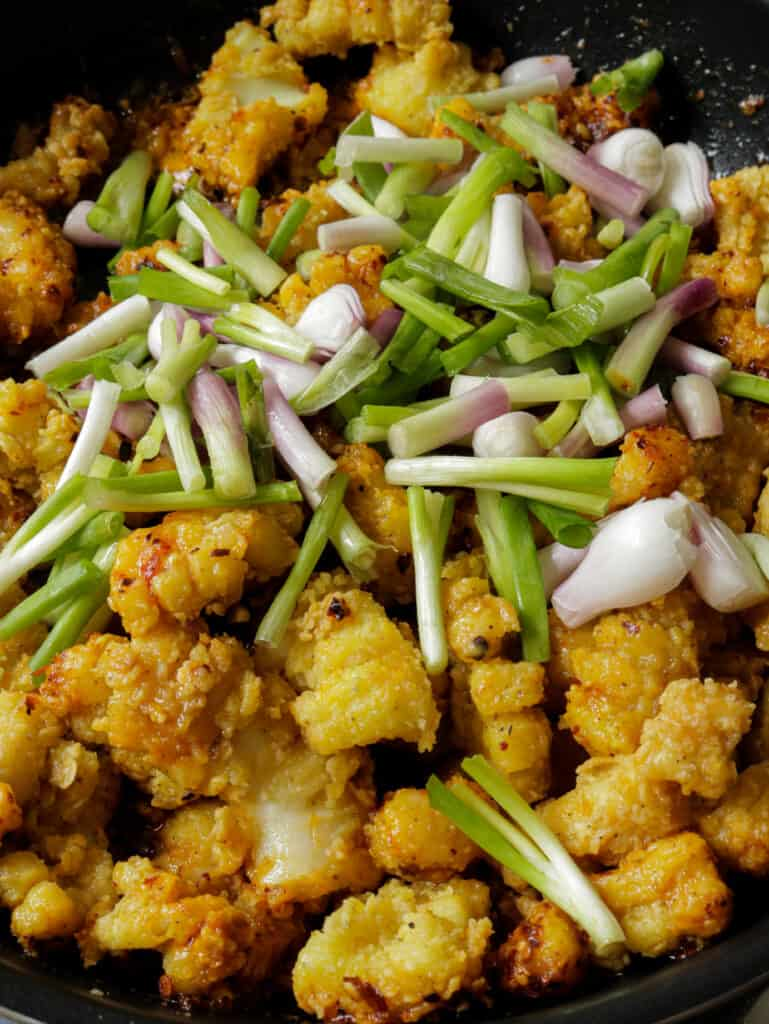adding scallions to the fried cuttlefish.