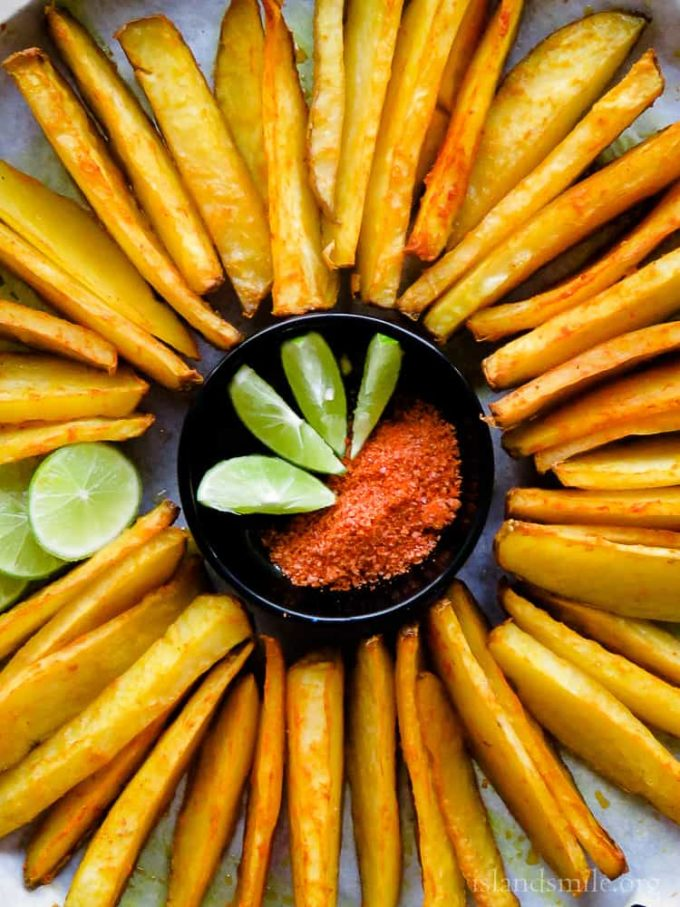 Crispy Oven-baked Potato wedges mixed with red chilli powder and turmeric.