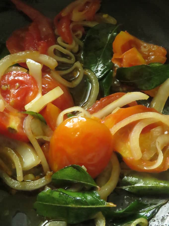 cooking onions, curry leaves, tomatoes in a pot with a few tablespoons of oil.
