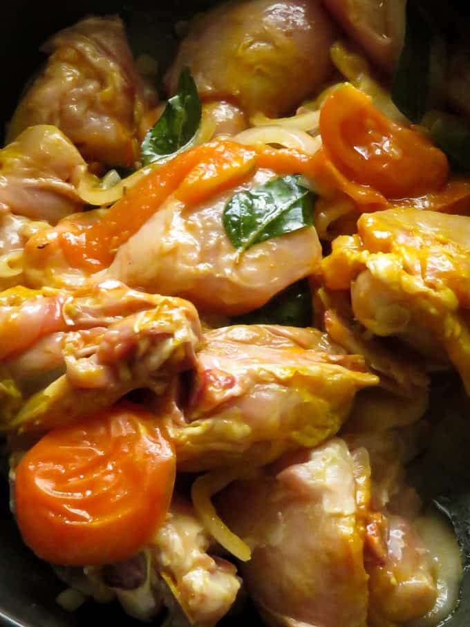 add the chicken parts to the onions and tomatoes cooking in the pan.