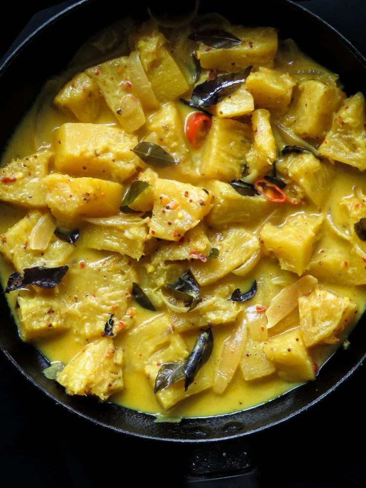 chunks of pineapple cooked in creamy coconut milk and served on a dish.
