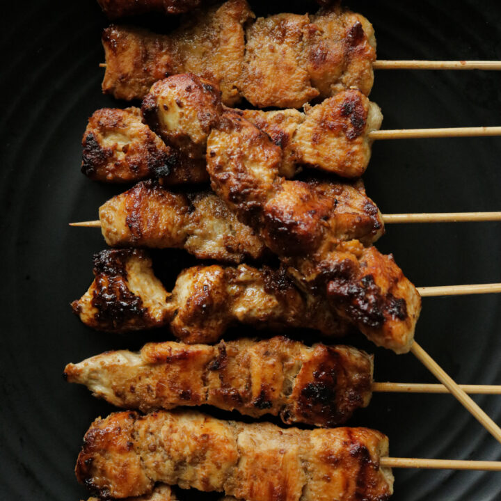 chicken satay grilled over a stove top.