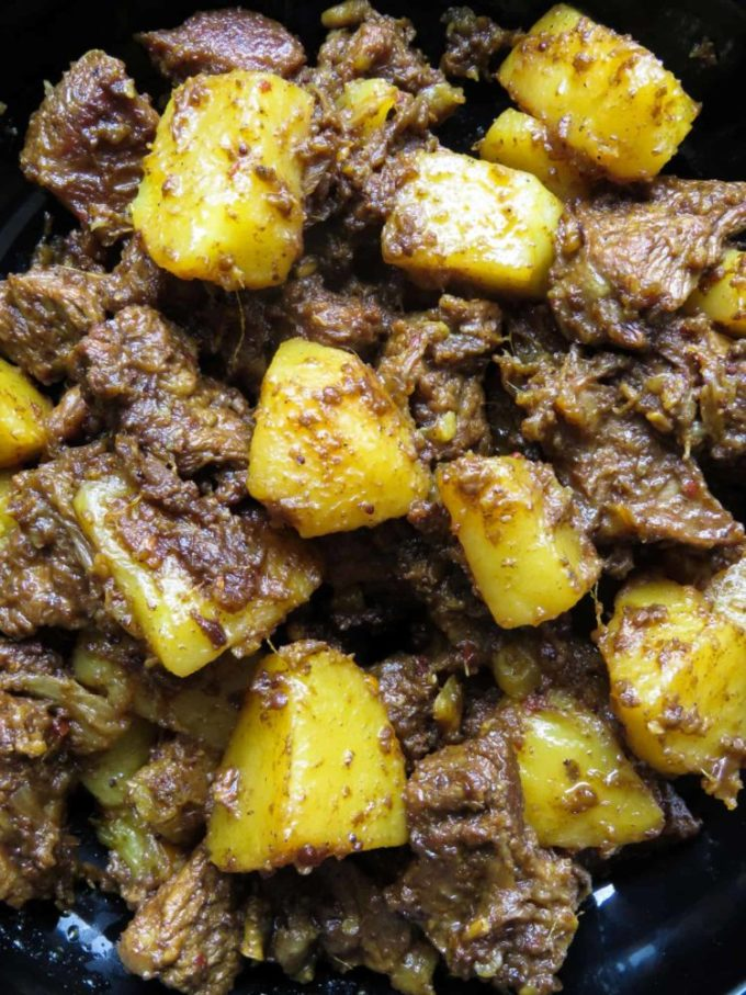 Slow cooked Indian beef and potato curry- tender meat and potatoes cooked in spices to flavor the dry gravy. this rich curry just needs a few garlic naans, roti or paratha to serve as a meal. #curry #beef #indian #meal #lunch #dinner #glutenfree #meal # potato