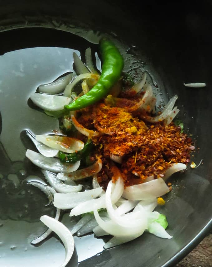 tempering onions, chillie powder, green chillie, turmeric to make the banana flower curry.