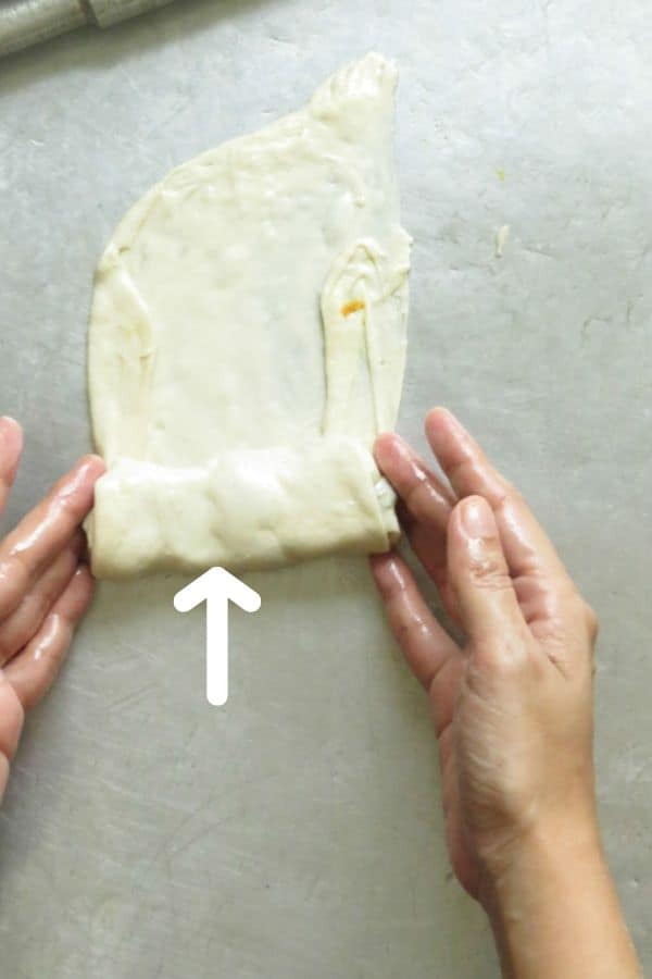 continue rolling the dough over the filling for the vegetable roti.