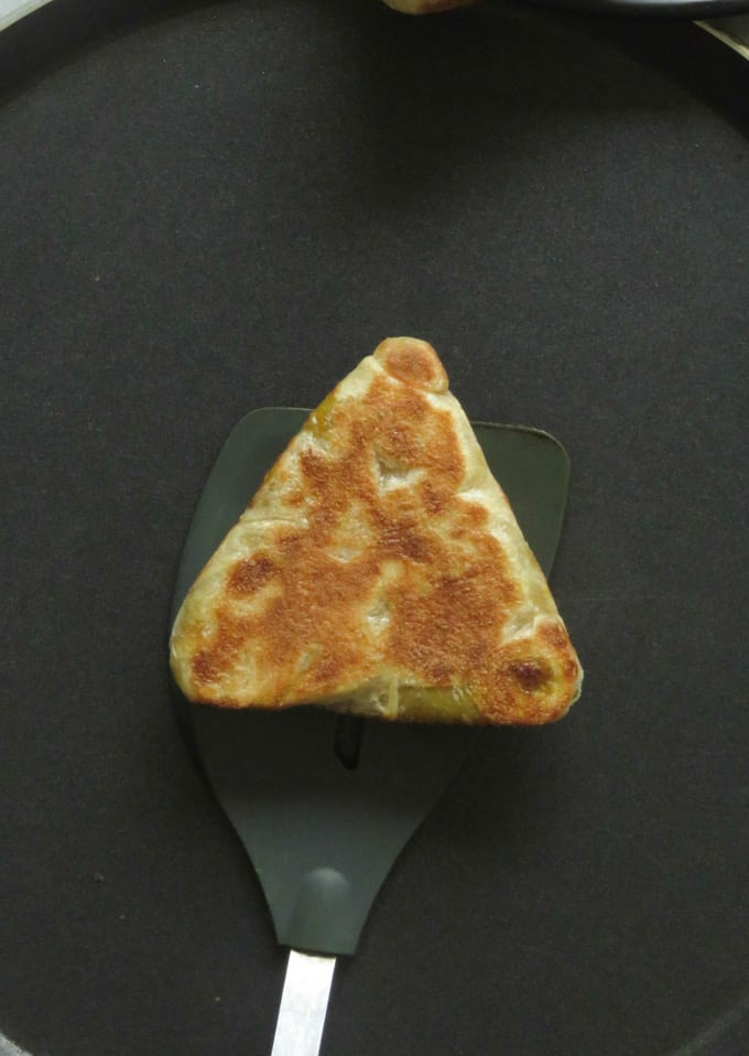 gently cooking the main sides of the triangle vegetbale roti.