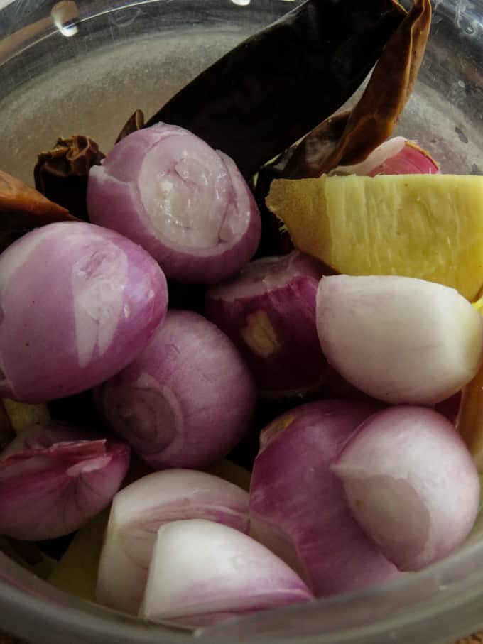 Adding the shallots, ginger, galangal, lemongrass,  garlic, turmeric to a blender to make the rendang paste.