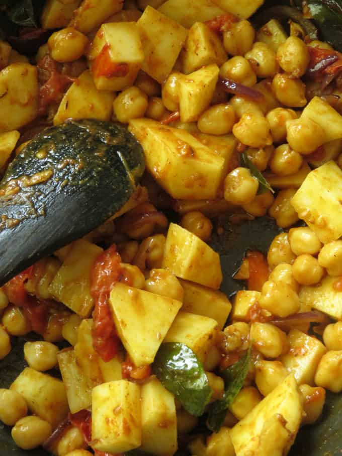 cooking potatoes and chickpeas in masala paste.