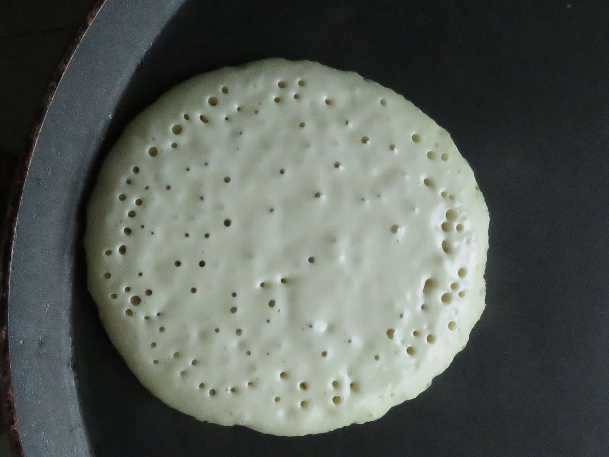 image shows tiny holes appearing on the pancakes as it cooks.