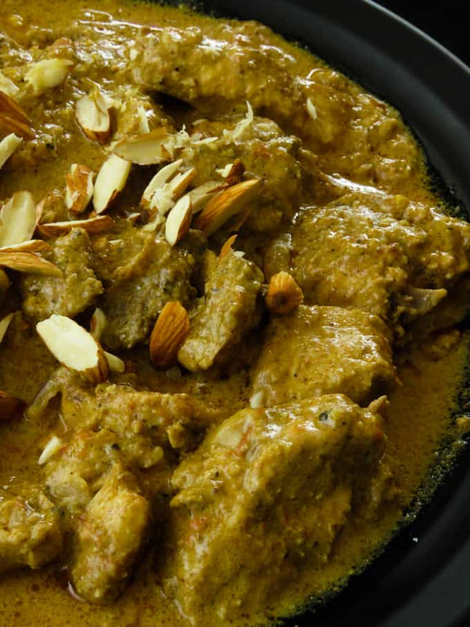badam chicken or almond chicken curry in a bowl with almond slices on top.