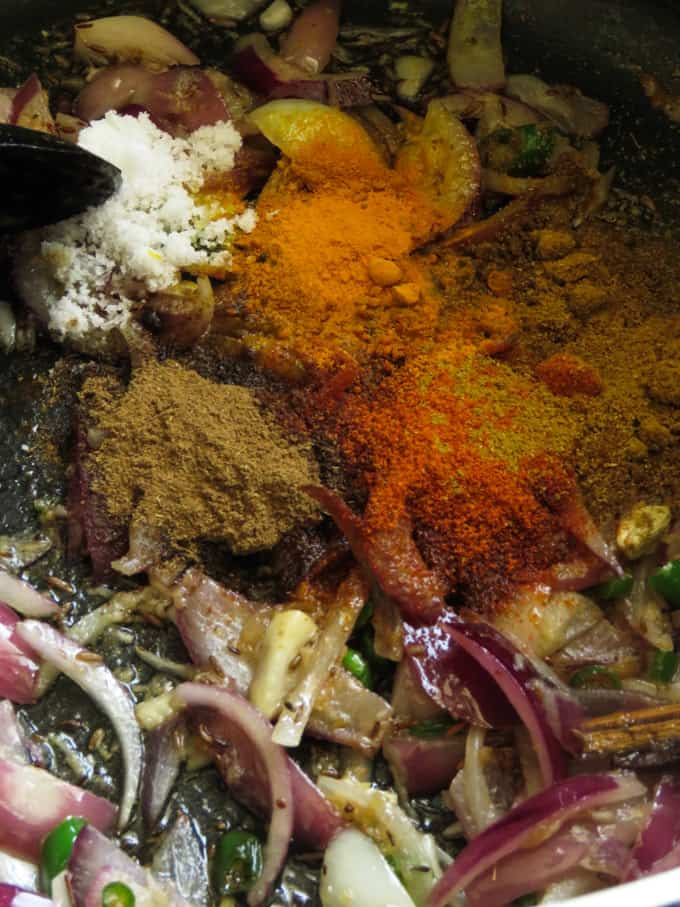 adding the spice powders to the frying onions to make the egg biryani masala.