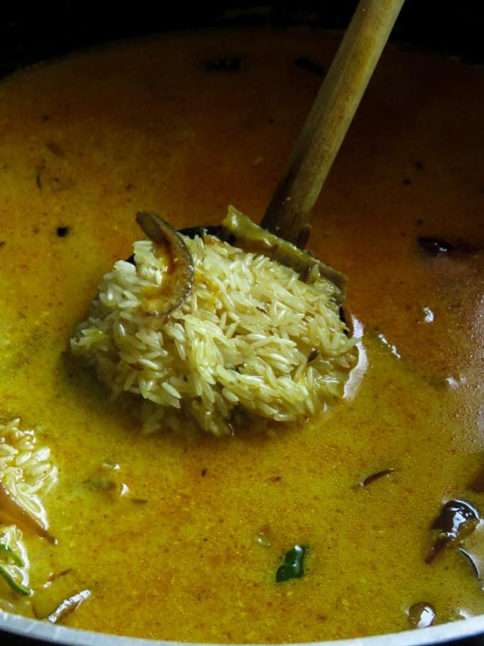adding water and basmati rice to the masala mix to make the biryani.