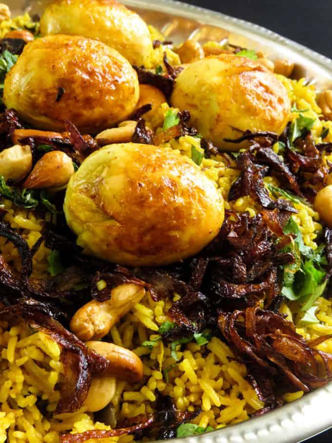 fried eggs, cashews and caremelized onions garnished over an egg biryani.