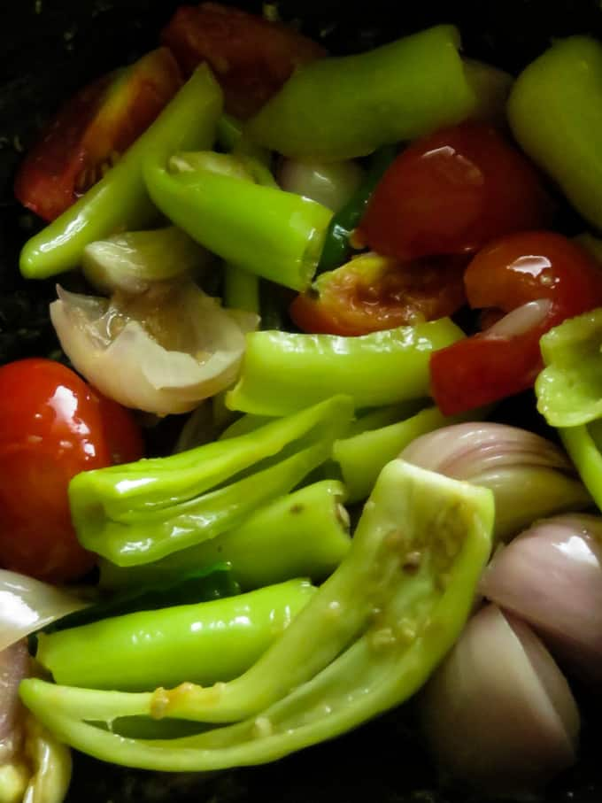 stir-frying the green peppers, onions and tomatoes to make the deviled fish.