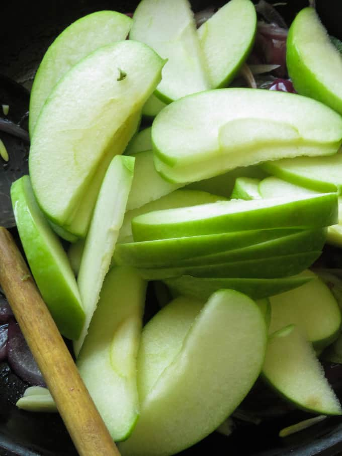 slices of apples stir-fried with onions and turmeric powder to make the apple stir-fry.