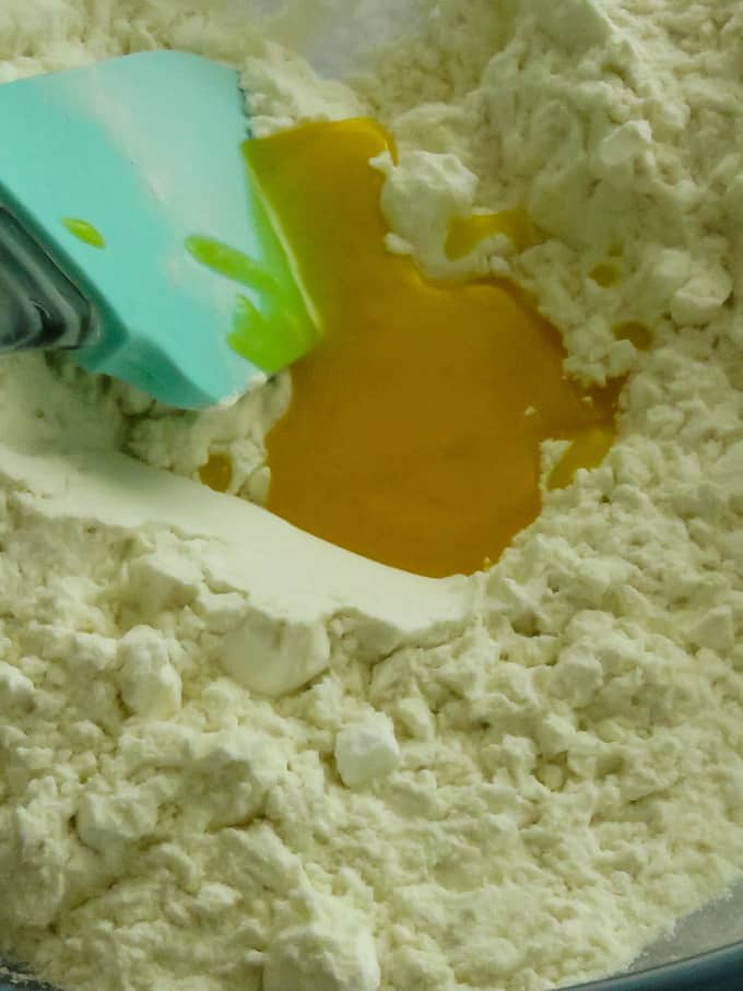 adding the ghee to the flour mixture to make the nankhatai.