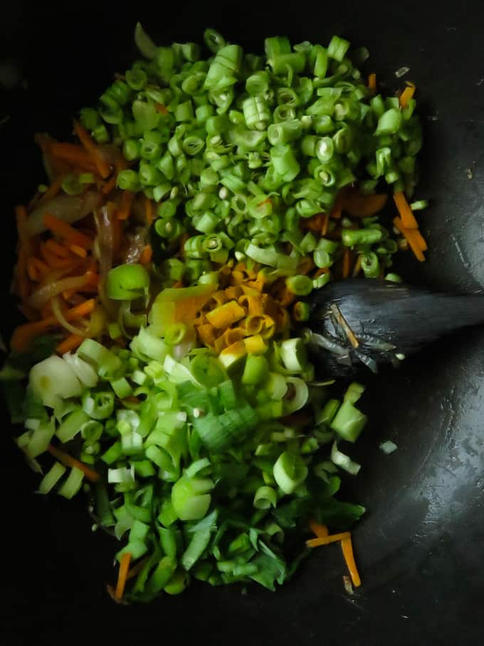 adding chopped beans and leaks to make the vegetable mixture for the fried rice.