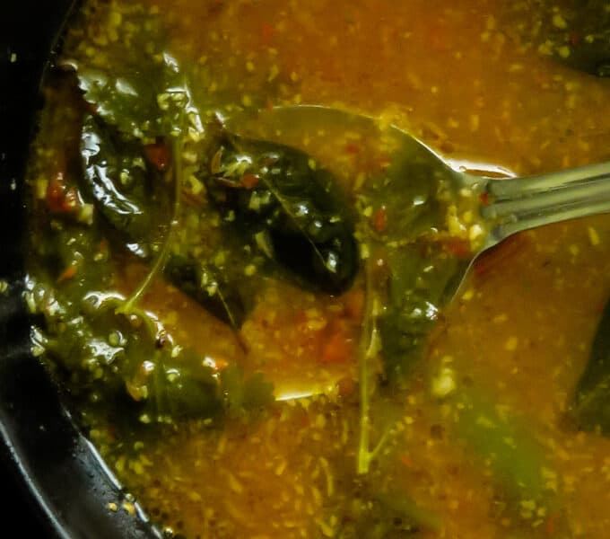 tomato rasam bowl with a spoon in the bowl