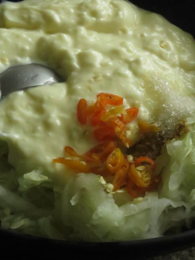 mixing grated cucumber, yogurt with cumin powder, chillies, seasoning and sugar to make the raita.