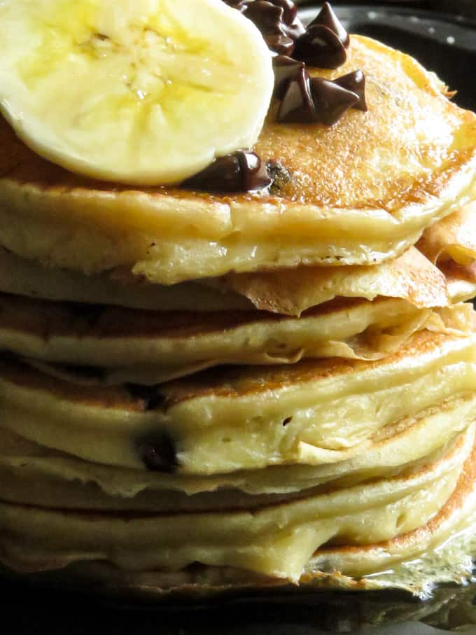 Fluffy banana pancakes with slices of banana and extra chocolate chips.