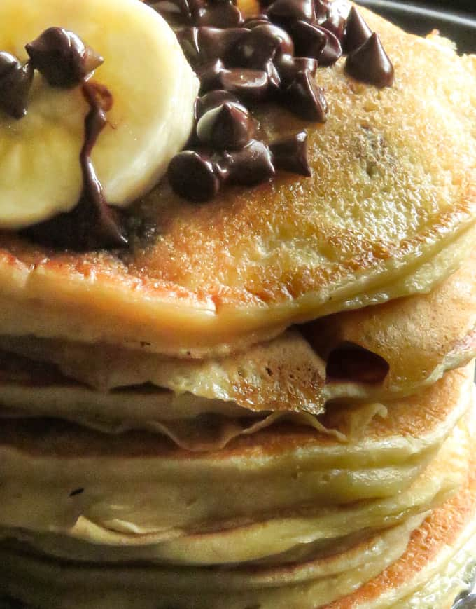 a stack of banana chocolate chip pancakes stacked with extra chocolate chips and slices of banana.
