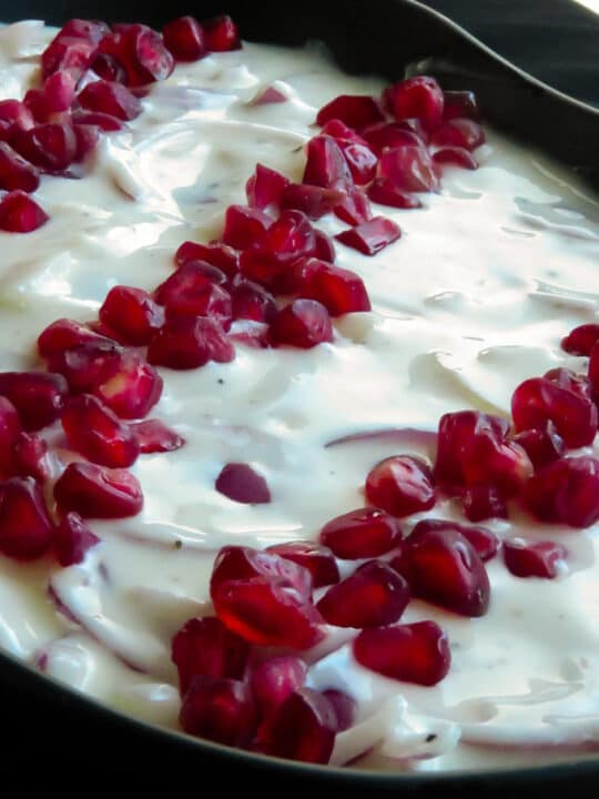 A bowl of onion raita made with yogurt and finely sliced onions and dottd with pomegranates.