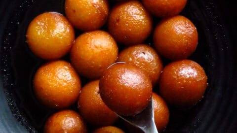 gulab jamuns on a plate with a spoon holding a gulab jamun