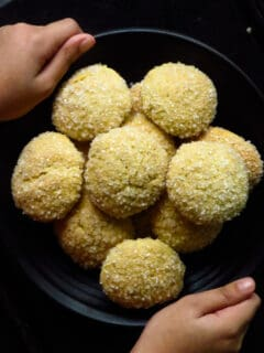 hands holding a plate of gnanakathai(sugar coated cookies)