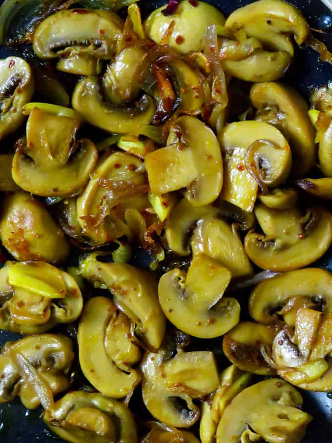 mushroom and onions sauteed in a frying pan