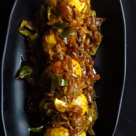 egg roast curry served in a flat black dish.