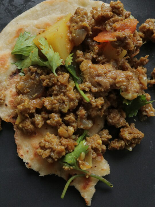 aloo keema on topped over a piece of naan roti,