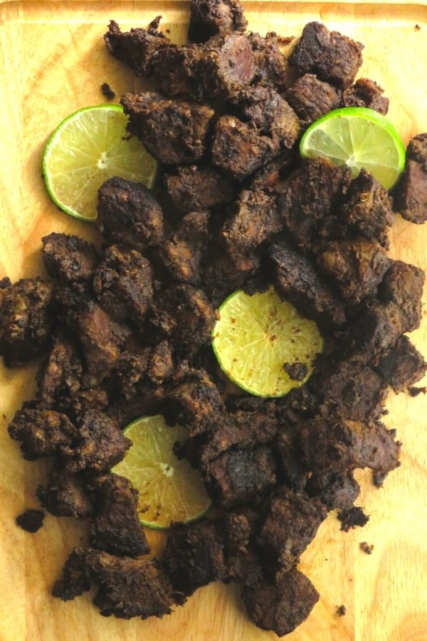Sri Lankan beef fry with lime wedges.